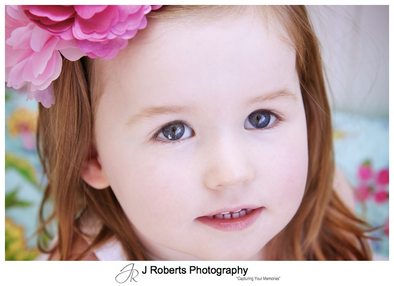 Portrait of a little girl with pink flowers in her hair - family portrait photography sydney