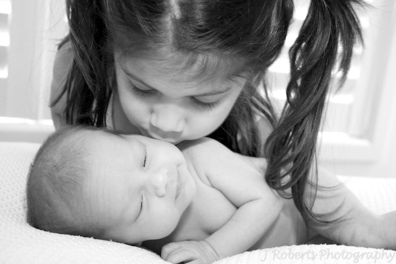 sister kissing newborn baby - newborn portrait photography sydney