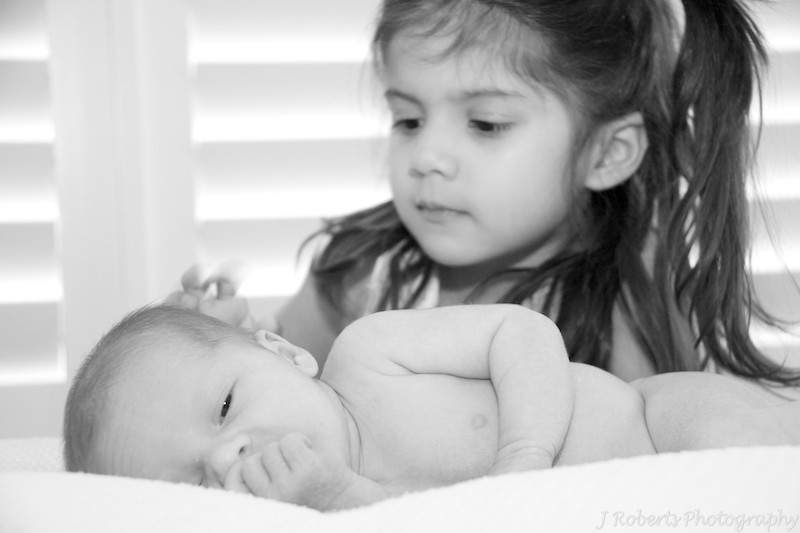 older sister patting newborn baby - baby portrait photography sydney