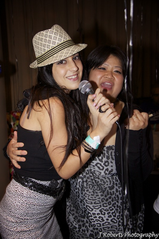 Couple singing karaoke at party - party photography