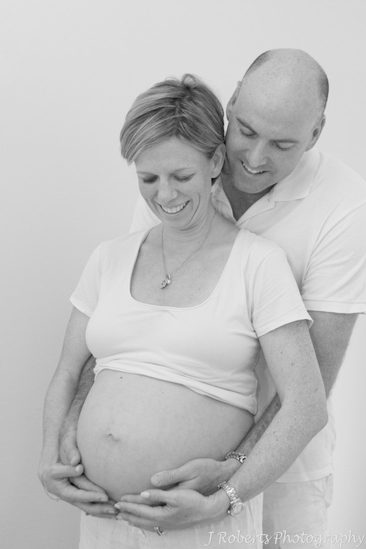 Couple smiling down at pregnant belly - B&W pregnancy portraits sydney
