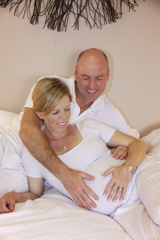 Pregnant couple smiling at belly