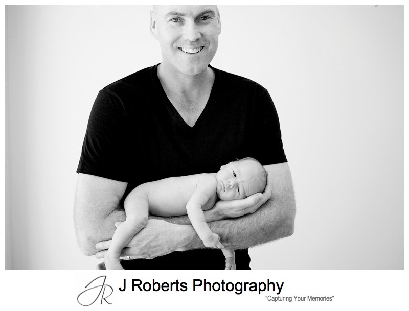 B&W portrait of a father with a newborn baby boy in his arms - newborn baby portrait photography sydney