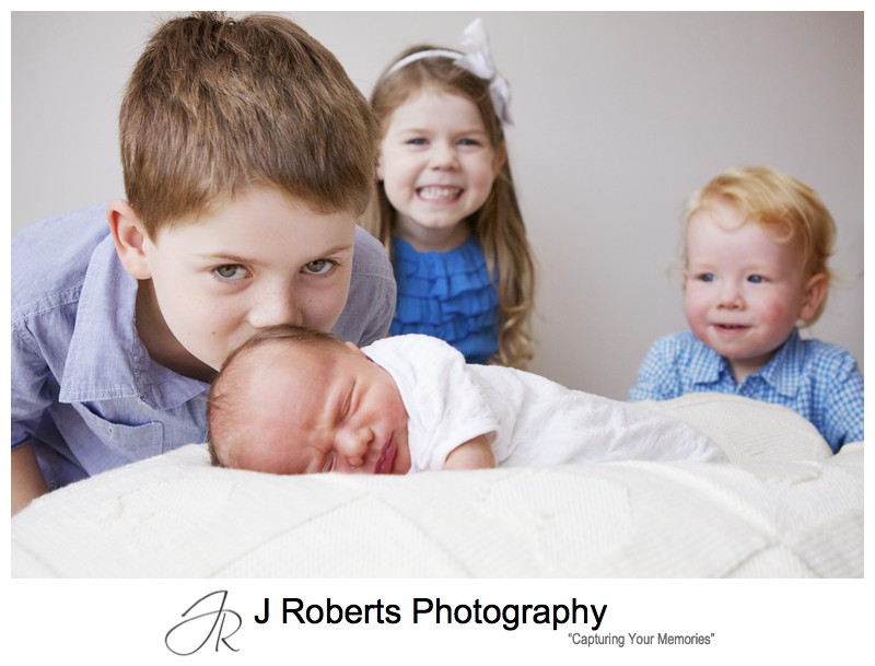 Bug brother kissing newborn babies head - newborn baby portrait photography sydney