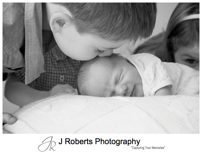 Smiling newborn as big brother kisses his head - newborn baby portrait photography sydney