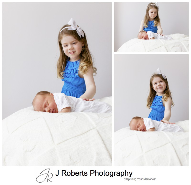 Big sister loving her newborn baby brother - newborn portrait photography sydney