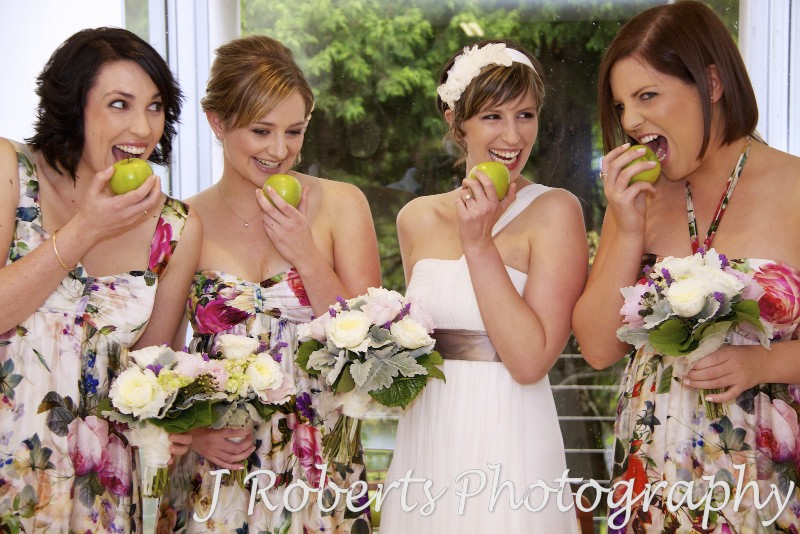 Bride mucking around with bridesmaids and apples - wedding photography sydney