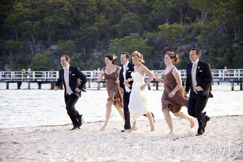 Bridal party running along the beach at Clifton Gardens Sydney - wedding photography sydney