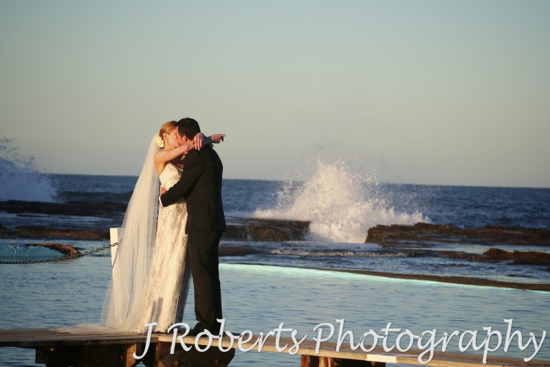 Bridal couple kissing at North Narrabeen Beach with breaking wave behind them - wedding photography sydney