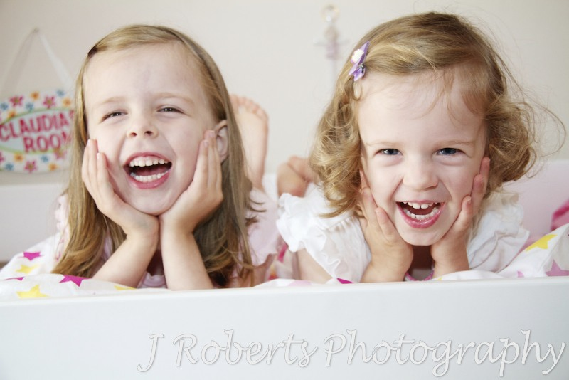 Sisters laughing together in their bedroom - family portrait photography sydney