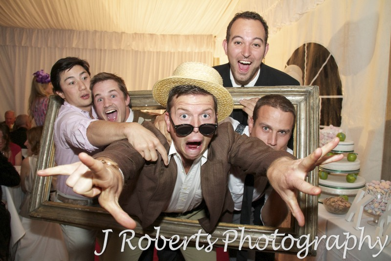 Guests mucking around with a frame at a party - party photography sydney