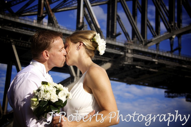 Bride and groom kissing in front of the Sydney Harbour Bridge - wedding photography sydney