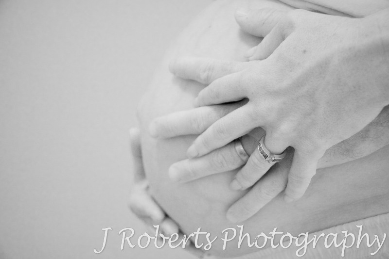 B&W of pregnant belly with parents hands on it - pregnancy photography sydney