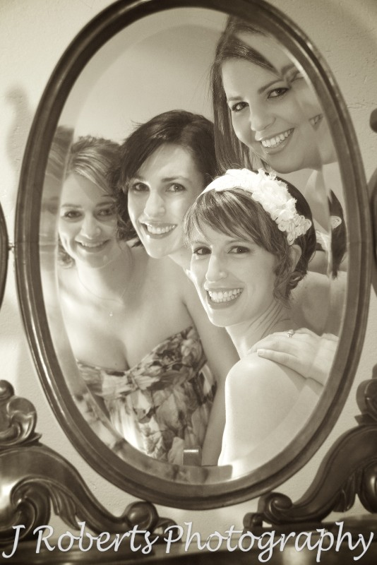 Sepia of bride and bridesmaids looking into an old fashioned mirror - wedding photography sydney