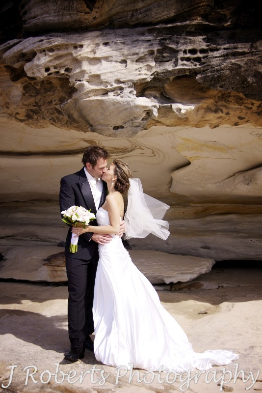 Bride and groom in front of a sandstone rock wall at Balmoral beach - wedding photography sydney