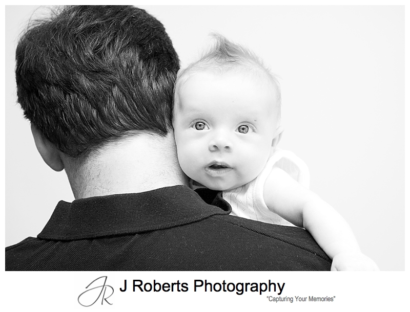 Baby girl looking over her daddy's shoulder - sydney baby photographer