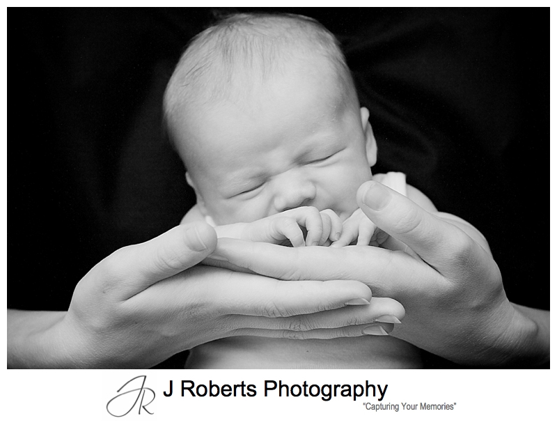 Black and white photo of a sleeping baby in his mothers hands- sydney baby portrait photographer