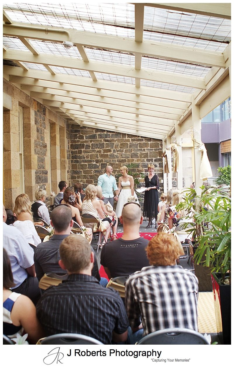 Wedding ceremony on the verandah of the old school house Sebel Kiama - sydney wedding photographer