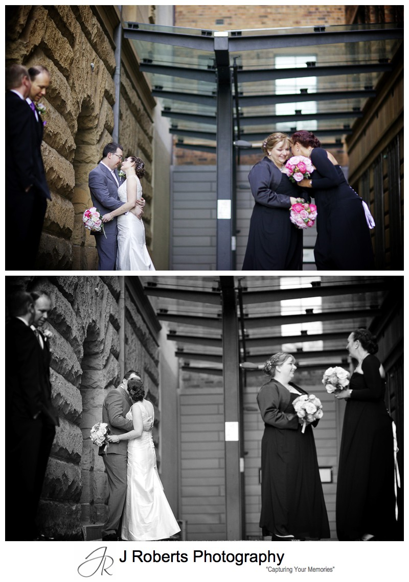 Bride and groom kissing with bridal party around - sydney wedding photography