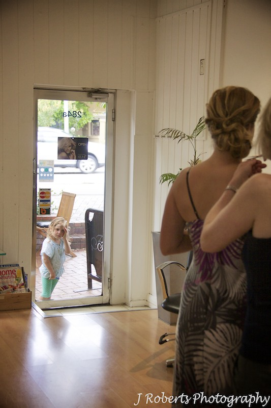 Little girl looking in window at bride having hair and make up applied - wedding photography sydney