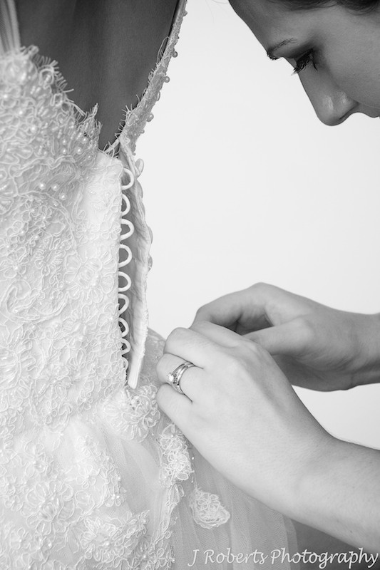 Bridesmaid doing up buttons on the back of brides dress - wedding photography sydney