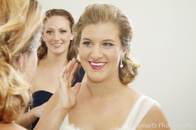 Bride putting earrings on in mirror with bridesmaid watching - wedding photography sydney