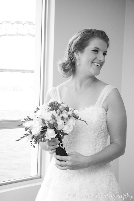 Bride holding bridal bouquet and smiling over her shoulder - wedding photography sydney