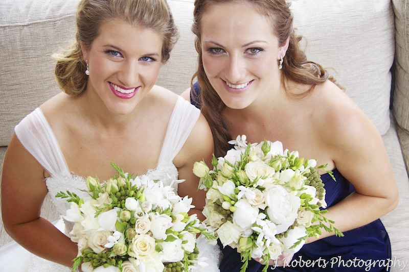 Bride and bridesmaid in blue smiling up at the camera - wedding photography sydney