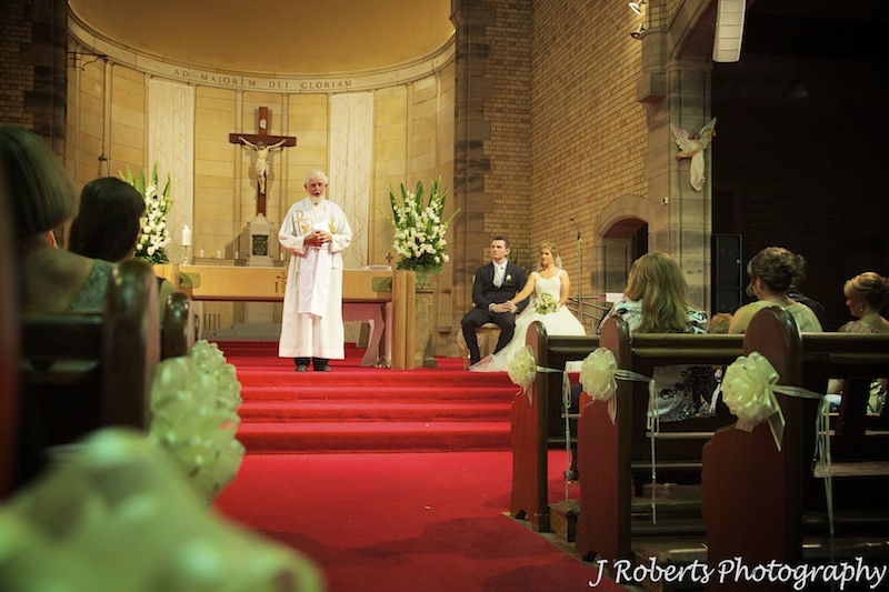 Bride and groom listing to sermon at St Mary's North Sydney - wedding photography sydney