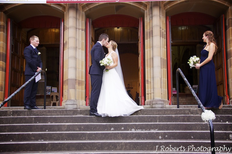 Bride and groom kissing outside church doors with attendants watching - wedding photography sydney