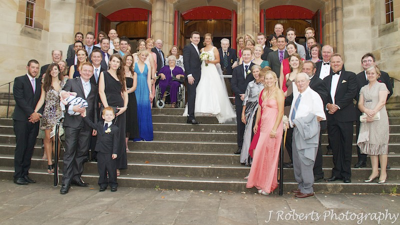Couple with all their guests on the church steps - wedding photography sydney