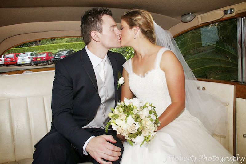 Couple kissing in back of the bridal car - wedding photography sydney