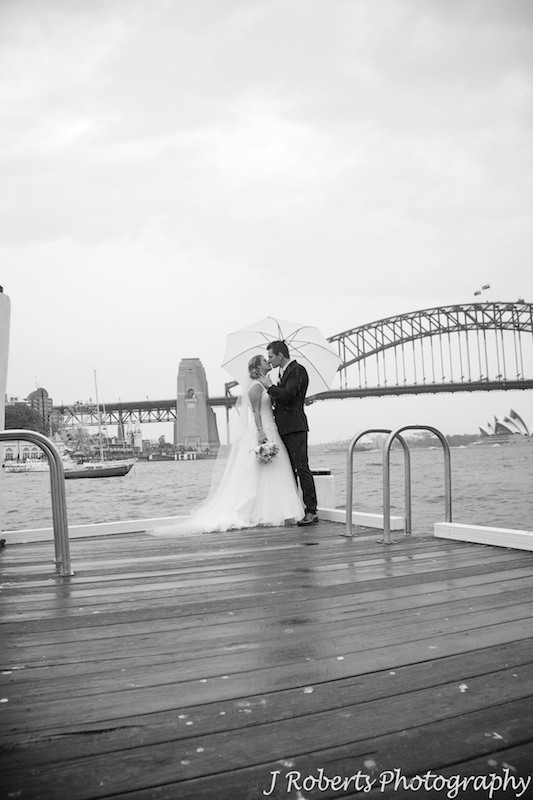Couple kissing on a pier Sydney Harbour = wedding photography sydney
