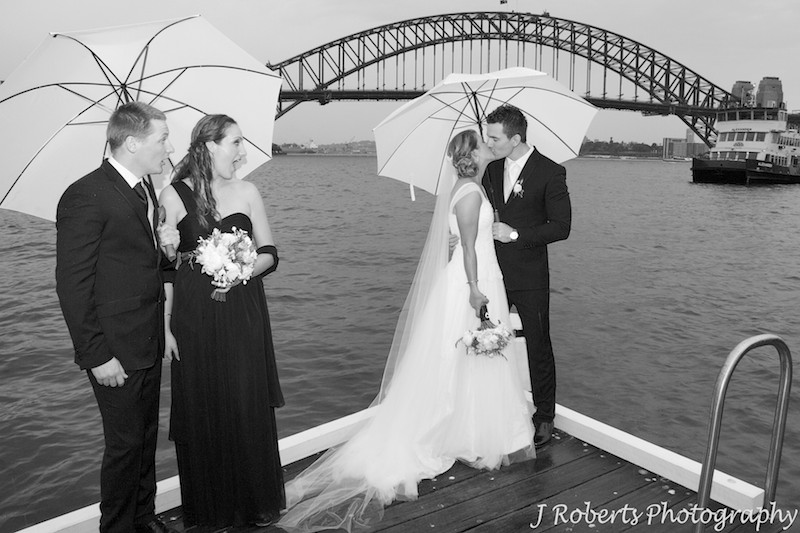 Bridal couple kissing and attendants looking shocked - wedding photography sydney