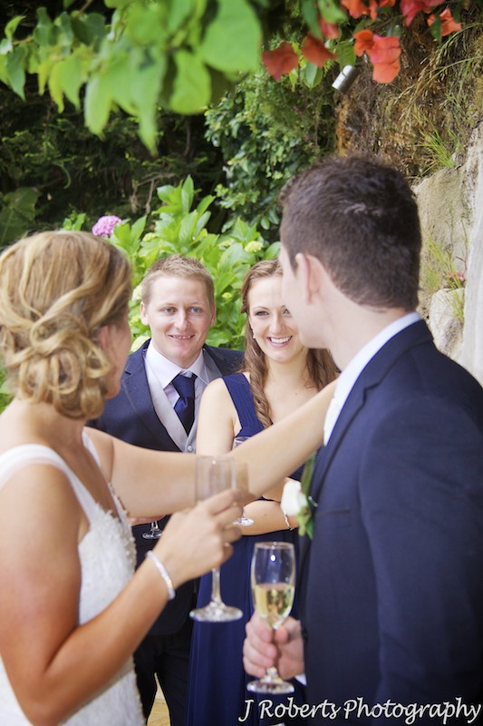 Best man and bridesmaid smiling at the couple in the distance - wedding photography sydney