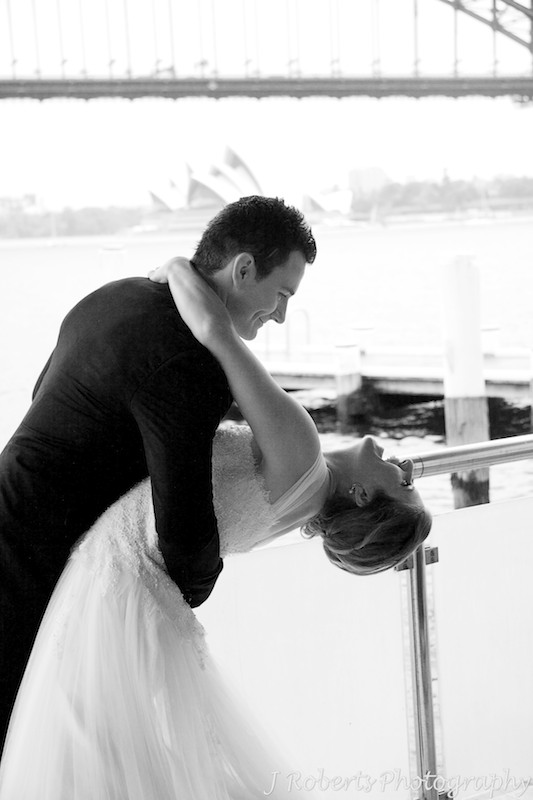 Groom dipping the bride in front of the Sydney Harbour Bridge - wedding photography sydney