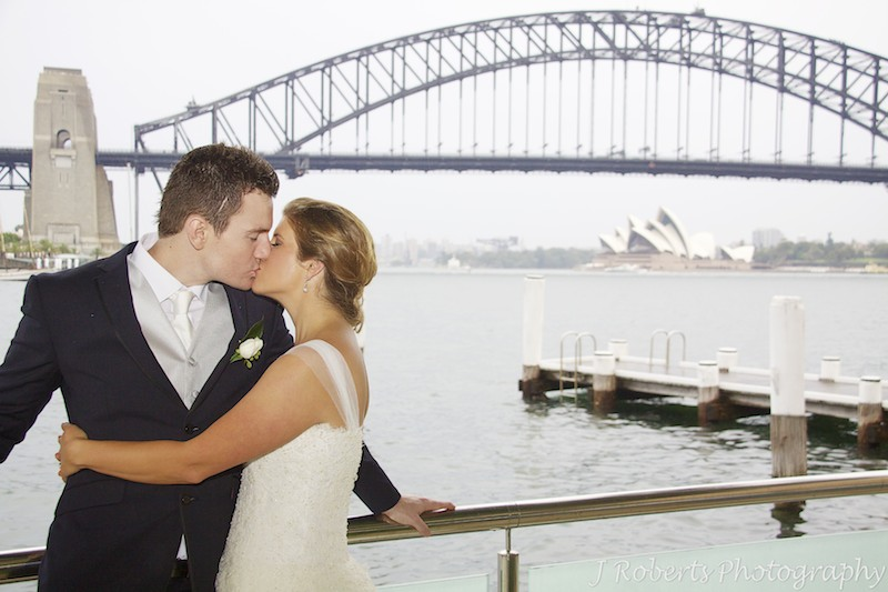 Couple kissing in front of Sydney Harbour - wedding photography sydney