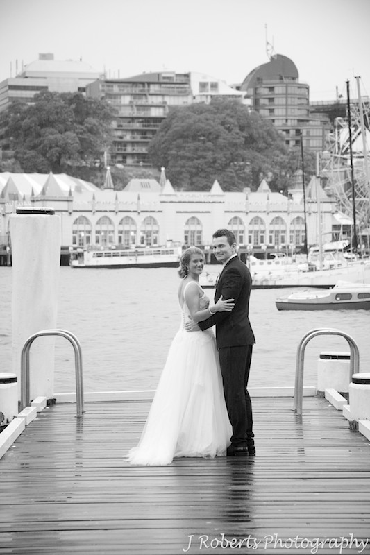 Couple walking on a pier and looking back at the camera - wedding photography sydney