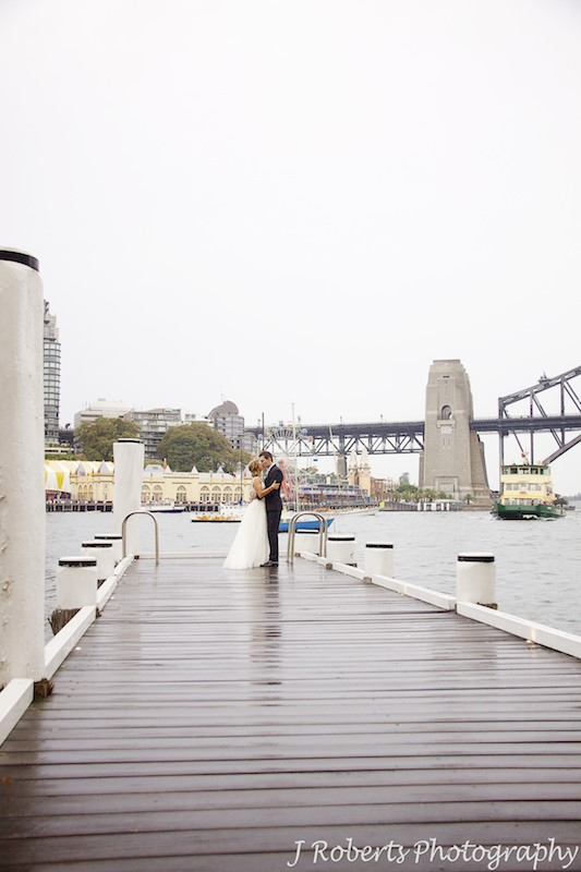 Couple kissing on a pier with Luna Park Sydney behind - wedding photography sydney