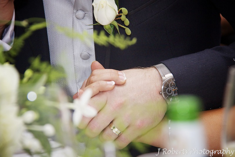 Couple holding hands during speeches - wedding photography sydney