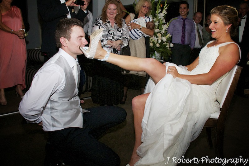 Groom using his teeth to take the brides garter off - wedding photography sydney
