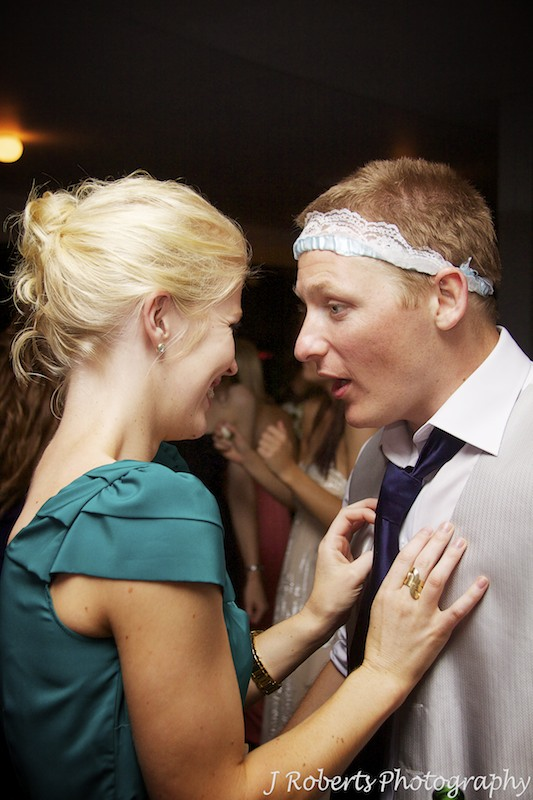 Best man talking to girlfriend after claiming the garter - wedding photography sydney