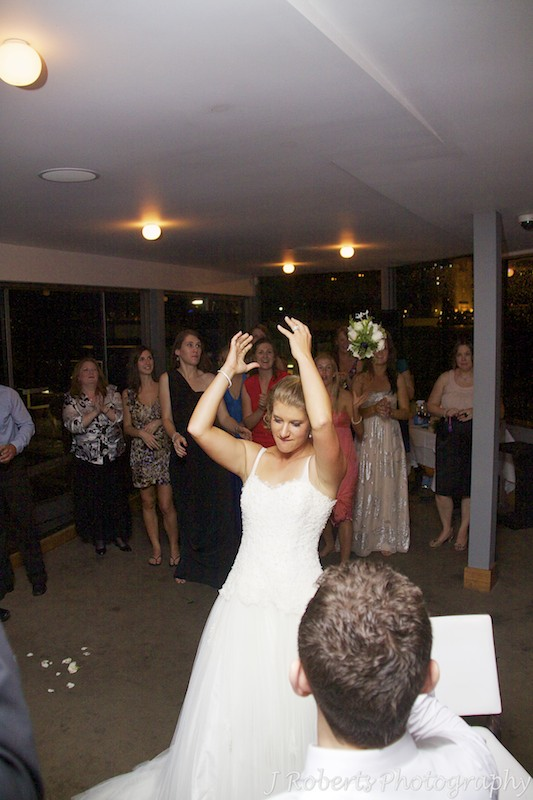 Bride throwing the bridal bouquet to single girls - wedding photography sydney