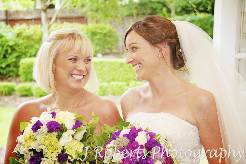 bride and bridesmaid having a laugh and fun - Wedding photography sydney