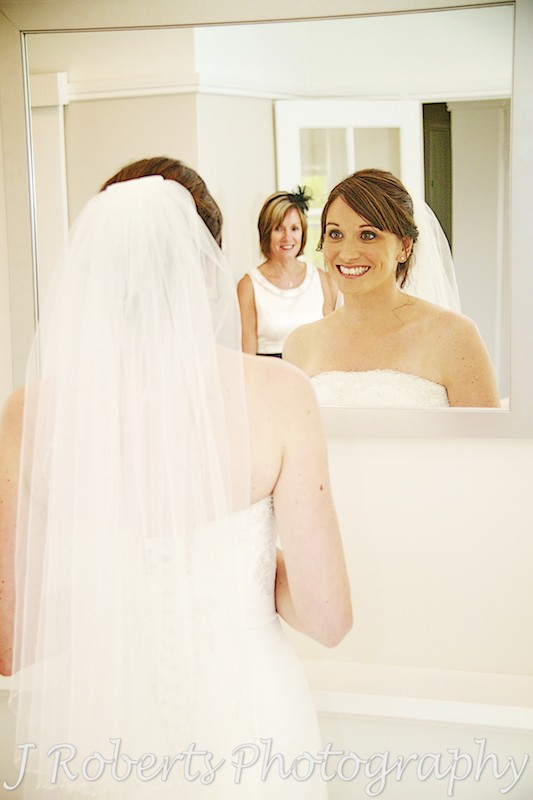 bride looking at herself in the mirror - wedding photography sydney
