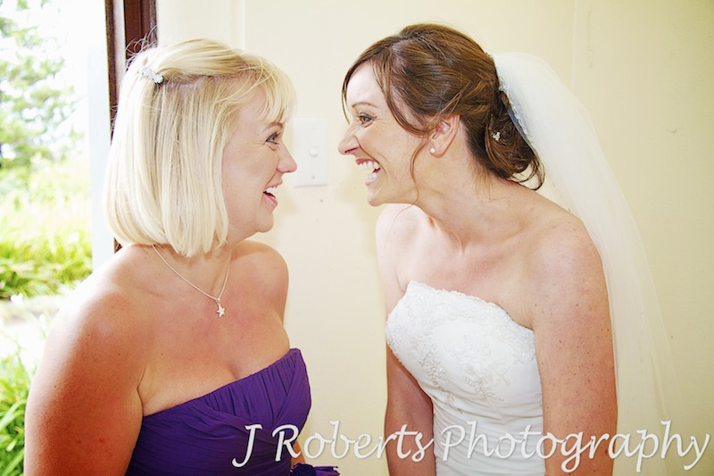 bride and bridesmaid share a joke and laugh - wedding photography sydney