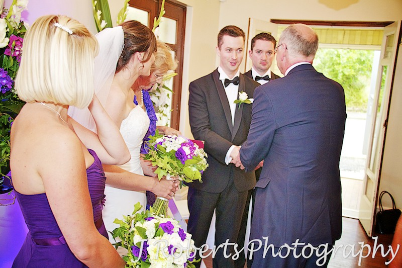 brides father shakes hand of groom and bridesmaid cries - wedding photography sydney