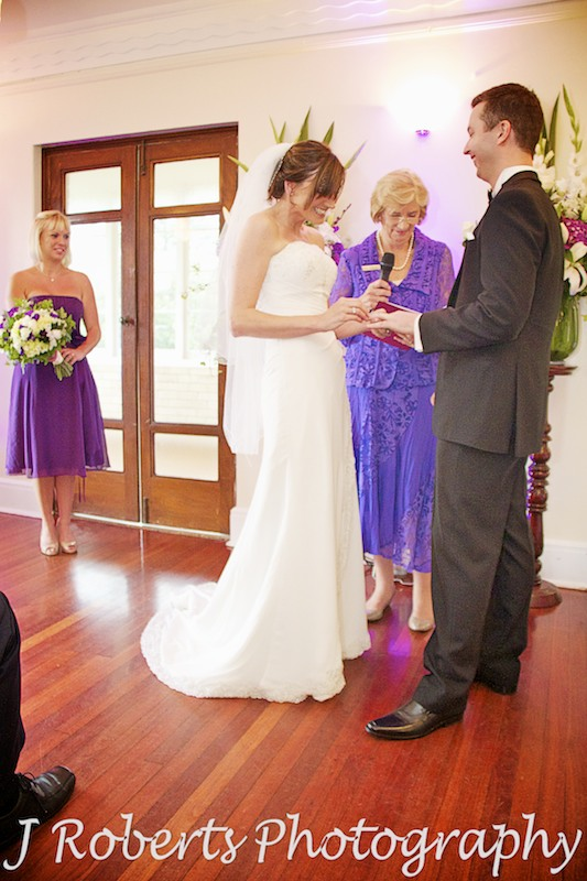bride putting ring on groom's finger - wedding photography sydney
