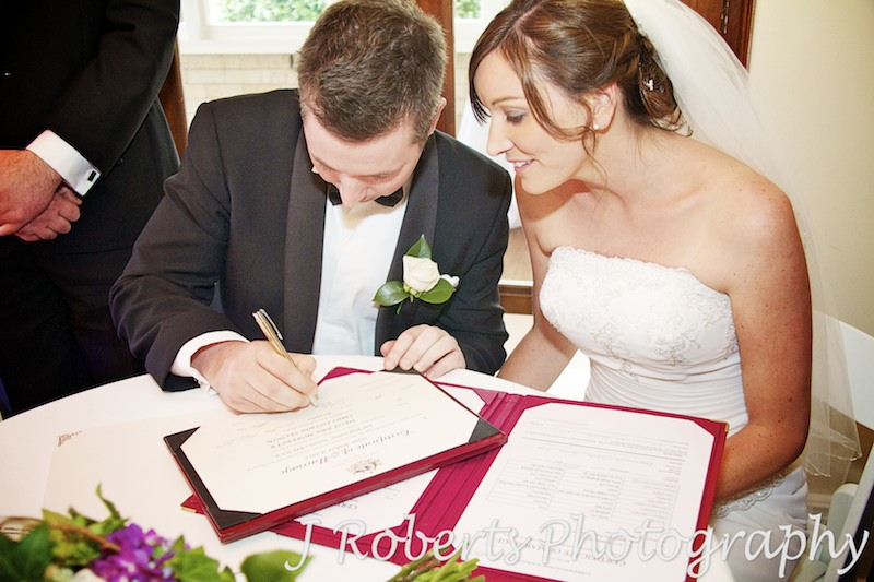 bride and groom signing the wedding certificate - wedding photography sydney