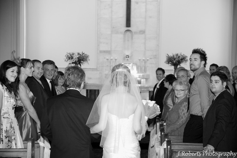 Bride walking down aisle and groom watching - wedding photography